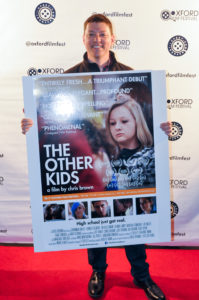 THE OTHER KIDS director Chris Brown proudly holds his film's poster on the red carpet. (Photo by Bill Dabney)