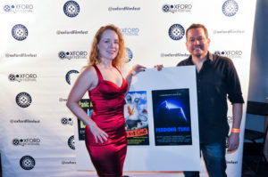 Jenifer and Kevin Studer pose with the poster for their film, FEEDING TIME (Photo by Bill Dabney)