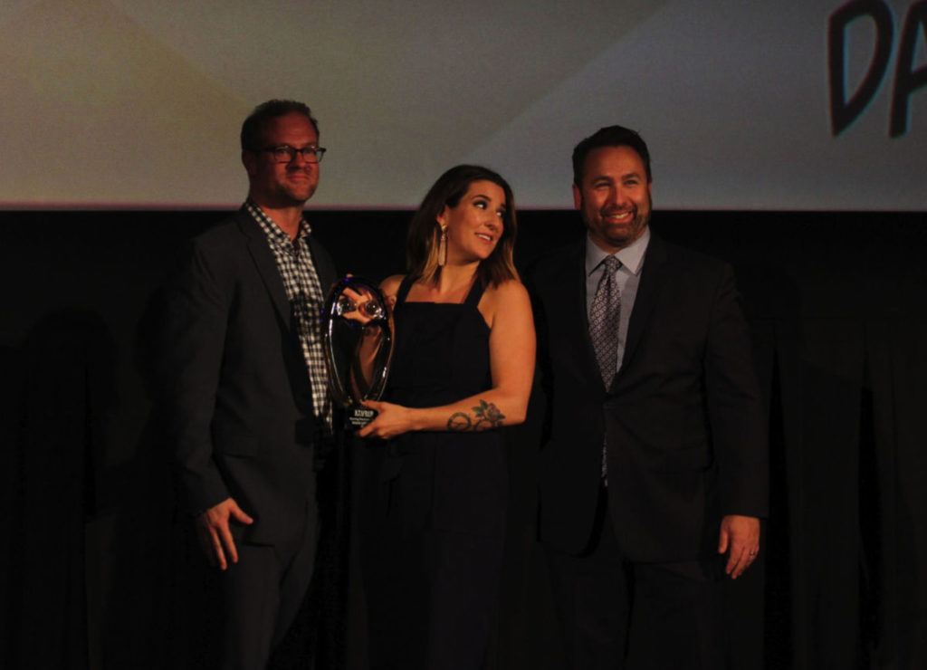 Paige Littere receives her award from Studio Movie Grill's Brandon Jones and Brian Schultz (Photo by Winston Henvey)