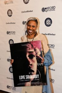 Astin Rocks shows off her poster for LOVE SOLILOQUY: A VISUAL ALBUM (Photo by Joey Brent)